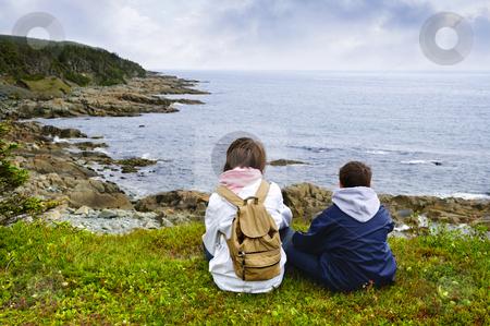 Children sitting at Atlantic coast in Newfoundland stock photo, Children looking at coastal view of rocky Atlantic shore in Newfoundland, Canada by Elena Elisseeva