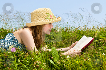 Young girl reading book in meadow stock photo, Young teenage girl reading book in summer meadow with straw hat by Elena Elisseeva