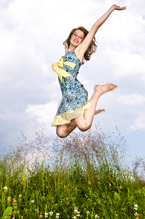 Young girl jumping in meadow stock photo, Young teenage girl jumping in summer meadow amid wildflowers by Elena Elisseeva