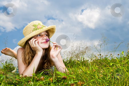 Young girl laying in meadow stock photo, Young teenage girl laying in summer meadow resting chin on hand smelling flower by Elena Elisseeva