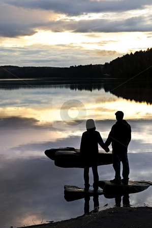 Silhouette of people watching sunset at lake stock photo, Sun setting over tranquil lake with people watching in silhouette by Elena Elisseeva