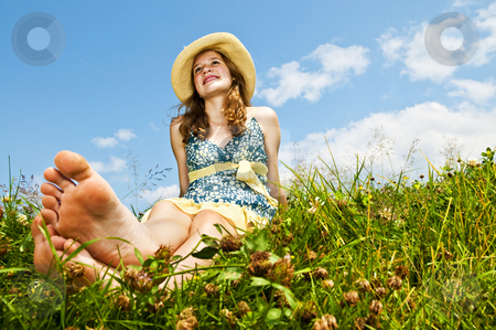 Young barefoot girl sitting in meadow stock photo, Young teenage girl sitting on summer meadow barefoot by Elena Elisseeva