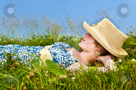 Young girl resting in meadow stock photo, Young teenage girl resting on summer meadow in straw hat by Elena Elisseeva