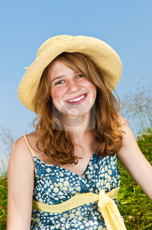 Portrait of young girl smiling in meadow stock photo, Portrait of young teenage girl smiling in summer meadow with straw hat by Elena Elisseeva