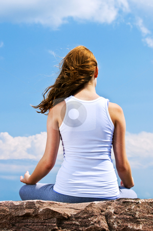 Young girl meditating outdoors stock photo, Portrait of young teenage girl practicing yoga outside by Elena Elisseeva