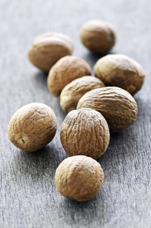 Whole nutmeg seeds stock photo, Whole nutmeg seeds on wooden table background by Elena Elisseeva