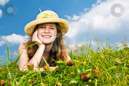 Young girl laying in meadow stock photo, Young teenage girl laying in summer meadow resting chin on hand in straw hat by Elena Elisseeva
