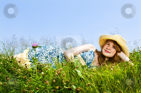 Young girl laying in meadow stock photo, Young teenage girl laying on summer meadow in straw hat by Elena Elisseeva