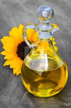 Sunflower oil bottle stock photo, Sunflower oil bottle with stopper and flower by Elena Elisseeva