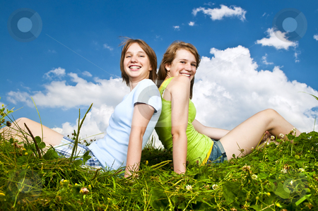 Young girls sitting in meadow stock photo, Two young teenage girl friends sitting back-to-back on summer meadow by Elena Elisseeva