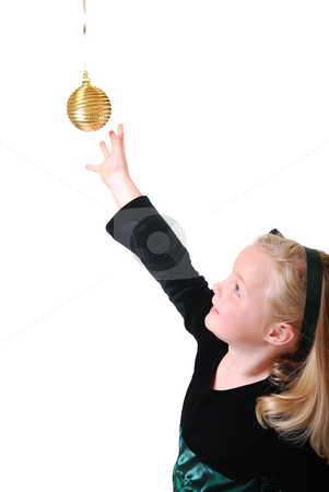 Girl reaching for ornament stock photo, Girl reaching for hanging ornament isolated on white by Christy Thompson