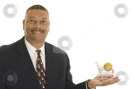 Global commerce stock photo, A smiling African American man holding miniature globe in a miniature shopping cart. by Christy Thompson