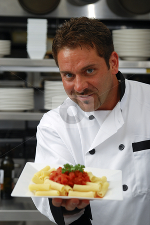 Smiling chef with plate of pasta stock photo, Attractive Caucasian chef holding a plate of pasta with red sauce in a restaurant kitchen. by Christy Thompson