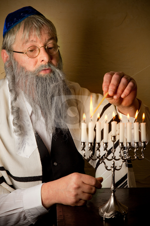Hannukah candles stock photo, Old jewish man lighting candles of a hannukah menorah by Anneke