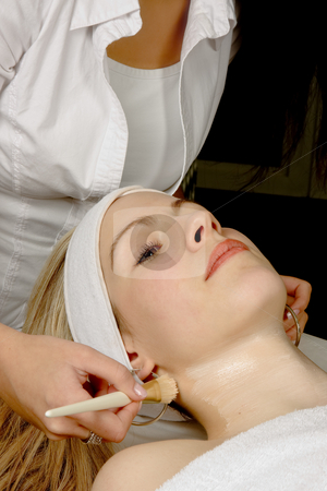 Beautician at work stock photo, Beautician giving a young woman a facial treatment by Anneke