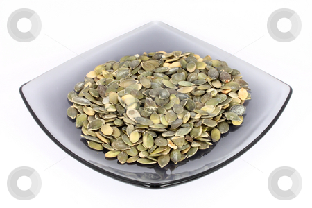 Pumpkin seed on glass plate stock photo, Pumpkin seed on glass plate, isolated on white by Borislav Marinic