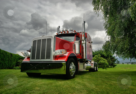 Semi Tractor Truck stock photo, A red semi tractor truck on a green lawn with dramatic clouds in background. by Timothy Epp