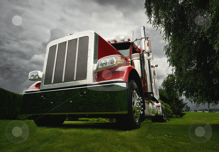 Modern Semi Tractor stock photo, A red semi tractor truck on a green lawn with dramatic clouds in background. by Timothy Epp