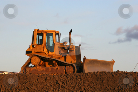 Idle bulldozer  stock photo, A big yellow bulldozer standing on a crest against the sky by Johann Helgason