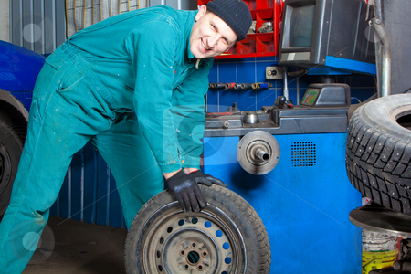Mechanic in garage stock photo, Mechanic changing car tire in garage by Ruta Balciunaite