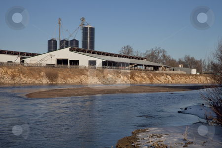 Cattle ranch buildings on river shore stock photo, Industrial barn and grain elevators of cattle ranch on shore of South Platte River in eastern Colorado by Marek Uliasz