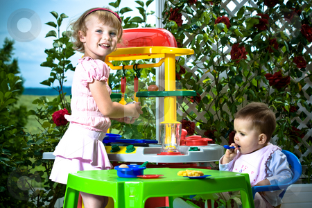 Kids and toy kitchen stock photo, A 6 month old baby and a 4 years old girl in front of toy kitchen by Val Thoermer