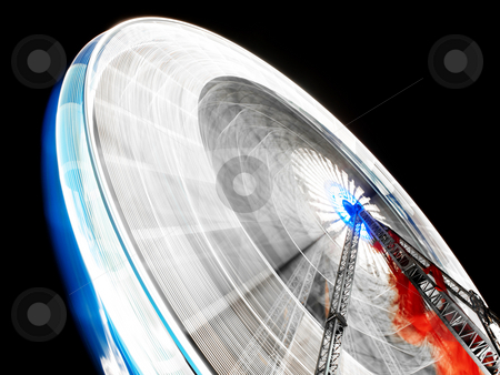 Ferris wheel at night stock photo, Rotating ferris wheel at night with blue and red colors by Laurent Dambies