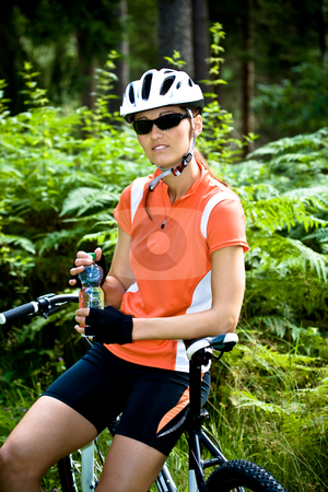 Cycling woman stock photo, Young cycling woman taking a break by Val Thoermer