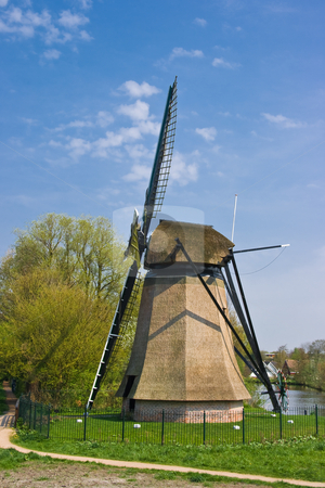 Dutch mill in city with houses in background stock photo, Dutch mill in city with residential houses in background on april afternoon by Colette Planken-Kooij