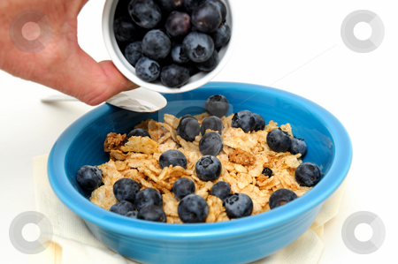 Pouring Blueberries On Cereal stock photo, Bowl of cold breakfast cereal with fresh blueberries on a white background by Lynn Bendickson