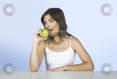 Apple diet stock photo, Beautiful young woman eating a green apple by ikostudio