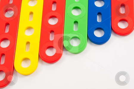 Background construction toys stock photo, Close up capturing brightly coloured components from a child's construction toy set arranged over white. by Samantha Craddock