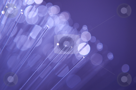 Background fibre optics stock photo, Close up and low level capturing the ends of many illuminated fibre optic light strands against a lavender colour. by Samantha Craddock