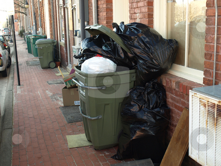Trash in the alley stock photo, A trsh can filled and waiting for pickup by Tim Markley