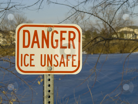 Danger ice unsafe sign stock photo, Danger ice unsafe warning sign with a frozen pond in background by Marek Uliasz