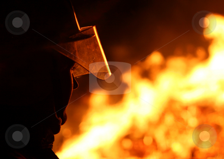 Firefighter stock photo, Silhouette of a firefighter facing a blazing fire by Jon Helgason
