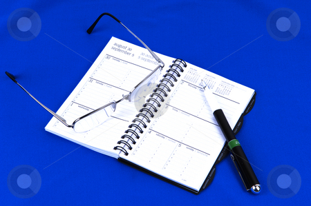 A day timer with glasses on blue. stock photo, A day timer and personal planer with glasses and a pen on royal blue background. by Horst Petzold
