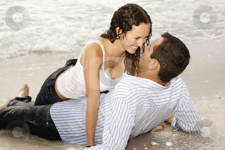 Beautiful couple laying on beach smiling at each other stock photo, Beautiful couple laying on the beach looking into each others eyes, smiling and happy. by Stephen Orsillo