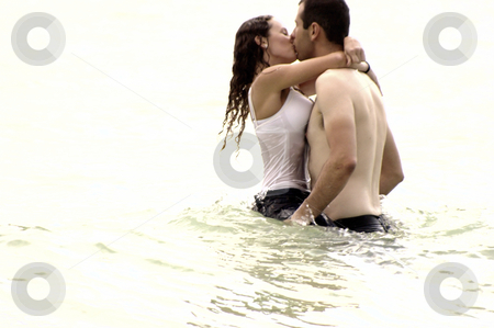 Clothed couple kissing in the ocean stock photo, High key image of young couple embracing and kissing  in the ocean, the water is up to their waists. by Stephen Orsillo