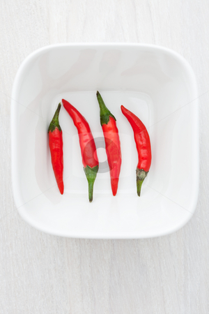 Four hot chili peppers stock photo, Four hot chili peppers in a white bowl by Robert Anthony