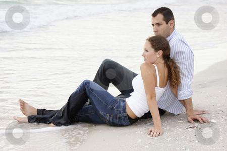 Young couple at waters edge with wet clothes stock photo, A handsome young american couple are sitting on the beach at the ocean's edge, fully clothed, their clothes are wet, their feet are in the water by Stephen Orsillo