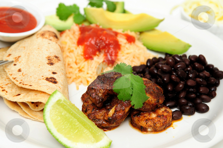 Shrimp Black Bean And Rice Plate stock photo, Shrimp cooked in Jamaican spices for tacos with black beans and Spanish rice, lime cilantro, cheese and hot sauce. by Lynn Bendickson