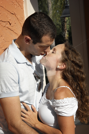Beautiful young lovers about to kiss in the afternoon sun stock photo, Beautiful young lovers holding each other about to kiss outdoors in the hot afternoon sun in tropical setting by Stephen Orsillo
