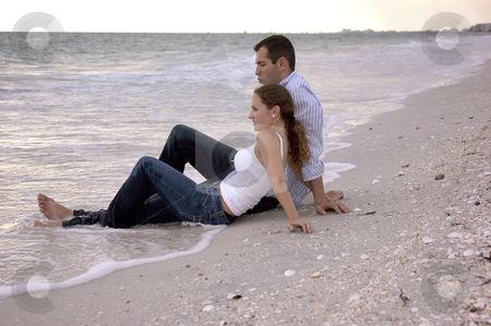 Beautiful couple at beach sitting in water clothed stock photo, A young couple on vacation are  at the beach sitting in the water, fully dressed as the sun begins to set, their legs are wet. by Stephen Orsillo