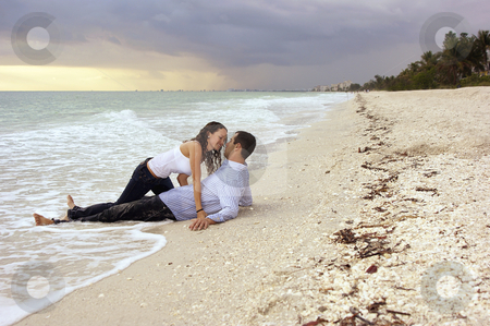 Fantasy woman about to kiss man  on beach at sunset stock photo, Man is laying on beach as woman crawls out of the water on top of him by Stephen Orsillo