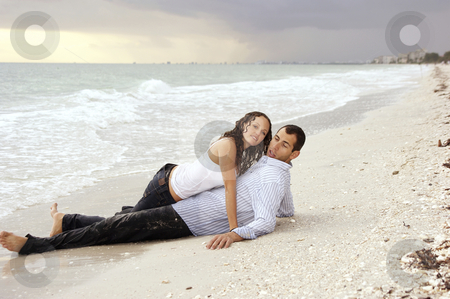 Woman laying on top of man at beach looking at viewer stock photo, A beautiful you lady is laying on top of a man at the beach, their clothes are wet and she is looking at viewer, he has strange expression on his face at sunset. by Stephen Orsillo
