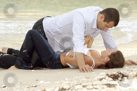 Woman is unbuttoning shirt on man as they lay on the beach stock photo, A beautiful young couple on the beach in wet clothes, the woman is laying on her back, the man is over her, she is unbuttoning his shirt. by Stephen Orsillo