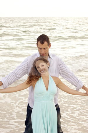 Beautiful happy young adult couple at the ocean with arms outstr stock photo, A young adult couple at the beach in the gulf of mexico with man standing behind the woman facing the viewer with arms outstretched with waves crashing behind them. Woman is smiling and looking at viewer. by Stephen Orsillo