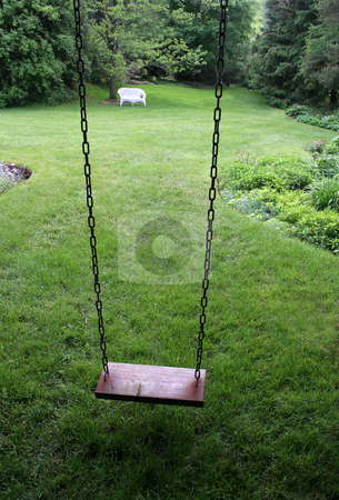 Yard Swing stock photo, An old wooden swing sitting in a lush backyard. by Chris Hill