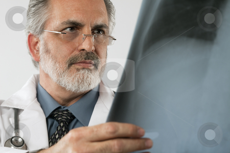 Doctor Looking at X-ray. Isolated stock photo, Cropped close-up portrait of a doctor wearing eyeglasses and a white lab coat and looking intently at an x-ray. Horizontal shot. Isolated on white. by Edward Bock